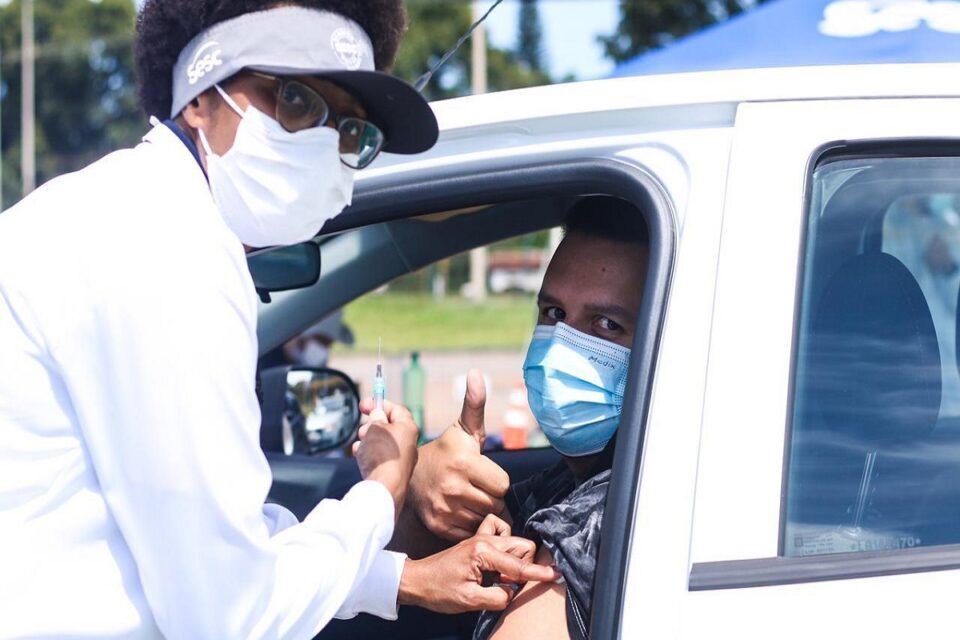 Profissional de saúde aplicando vacina contra a covid-19 em ponto de vacinação do Sesc-DF