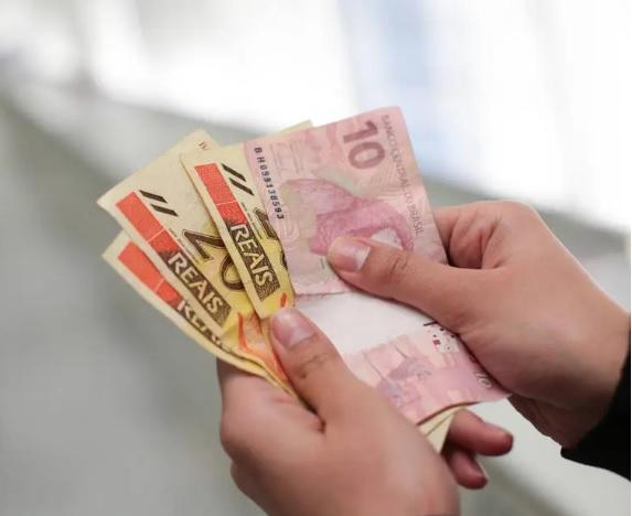 Mãos de mulher contando dinheiro. Notas de vinte e de dez reais