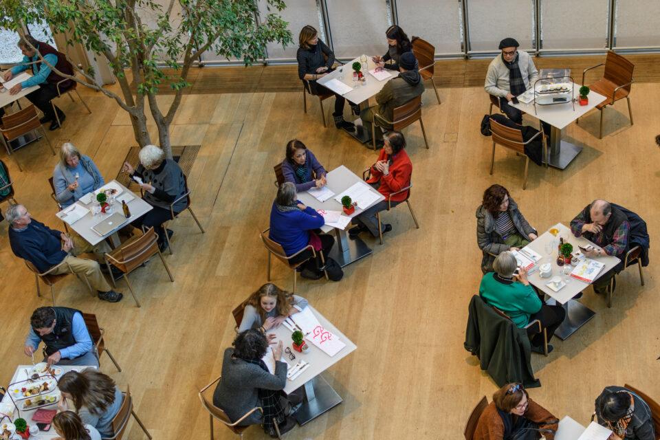 Restaurante com mesas de quatro lugares, forradas com tecido branco e piso de madeira