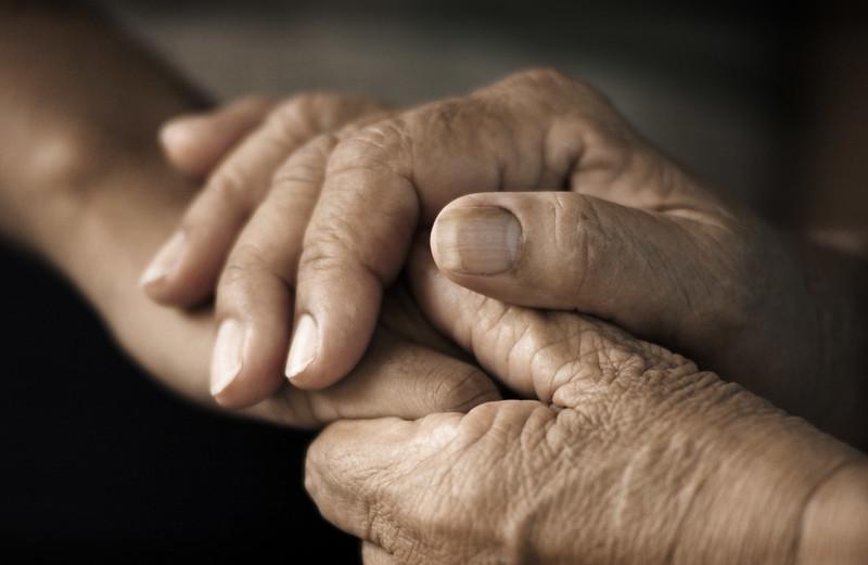 Mãos de idosos unidas em demonstração de afeto e acolhimento